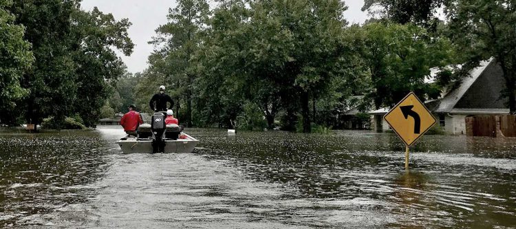 rescuers on boat on flooded street