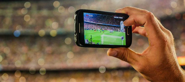 Holding mobile phone to take photo in stadium