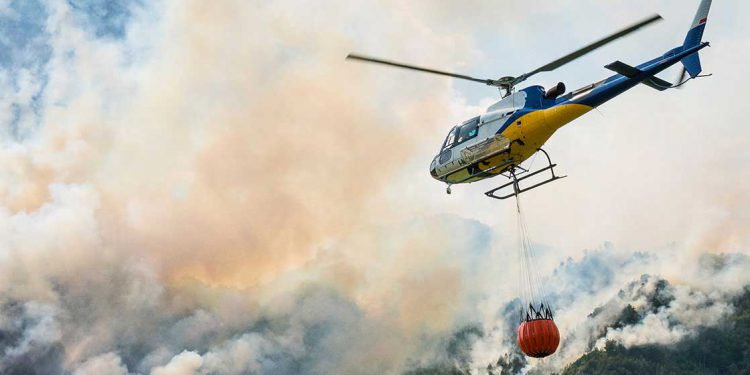 helicopter flying over wildfire smoke