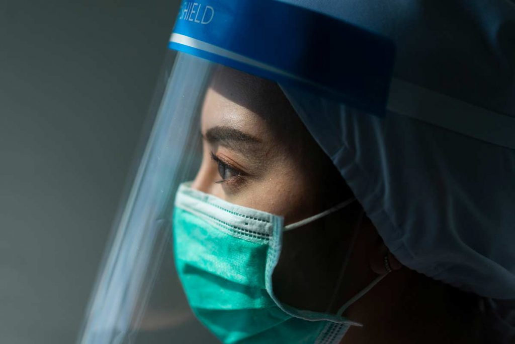 Healthcare worker wearing PPE and face shield